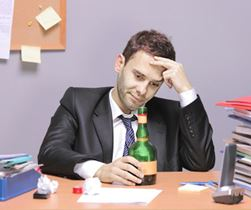 Man drinking alcohol while working