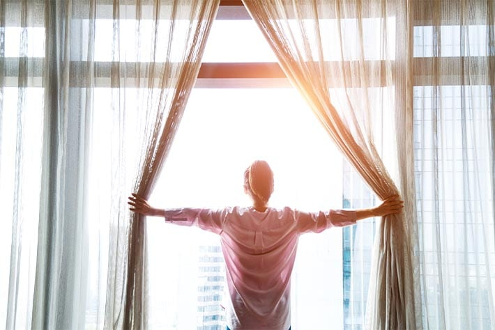 woman opening the curtains to a new day