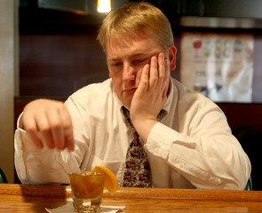 depressed looking man drinking in pub
