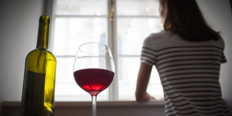 Woman drinking a bottle of red wine
