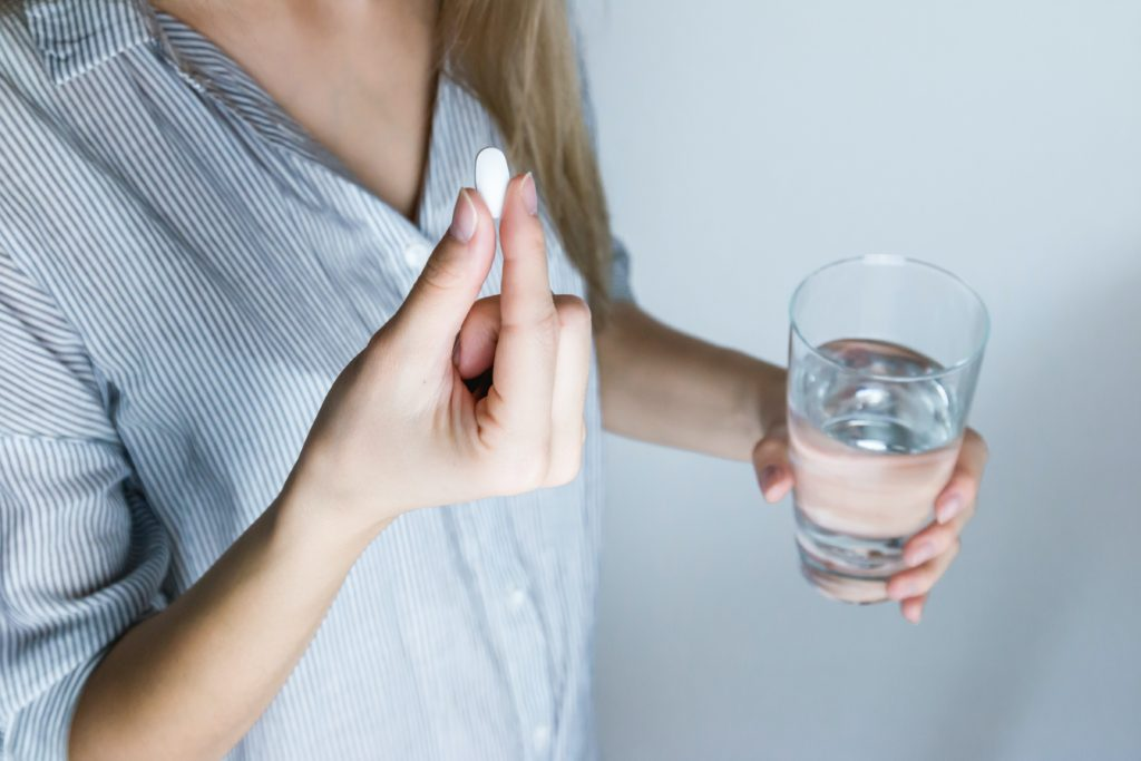 Woman taking tablet with water