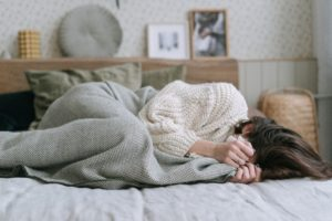Woman lying on the bed curled up upset